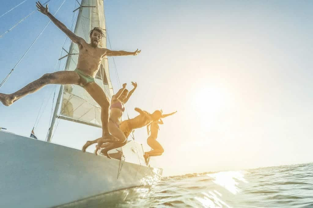 Friends diving into the sea off a boat