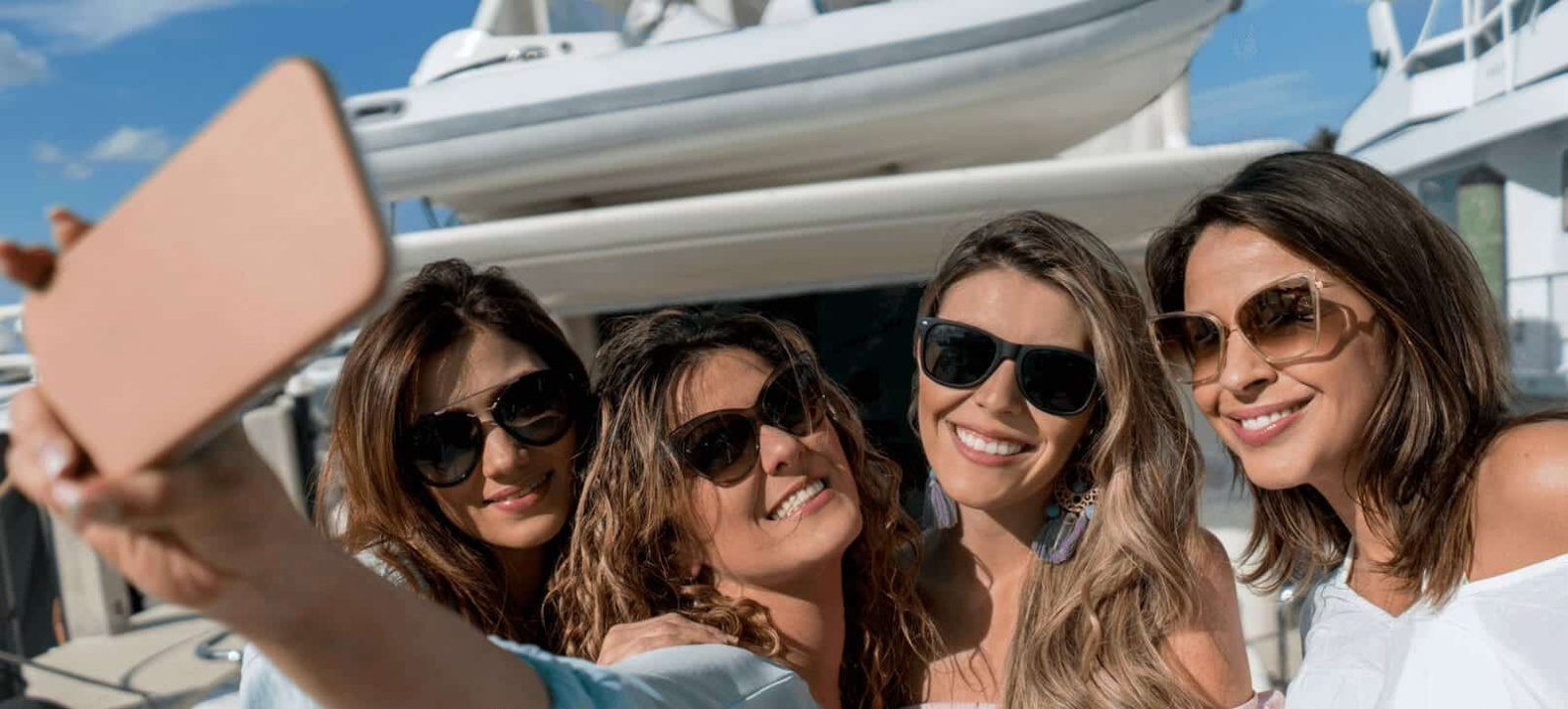 4 women taking selfie on boat